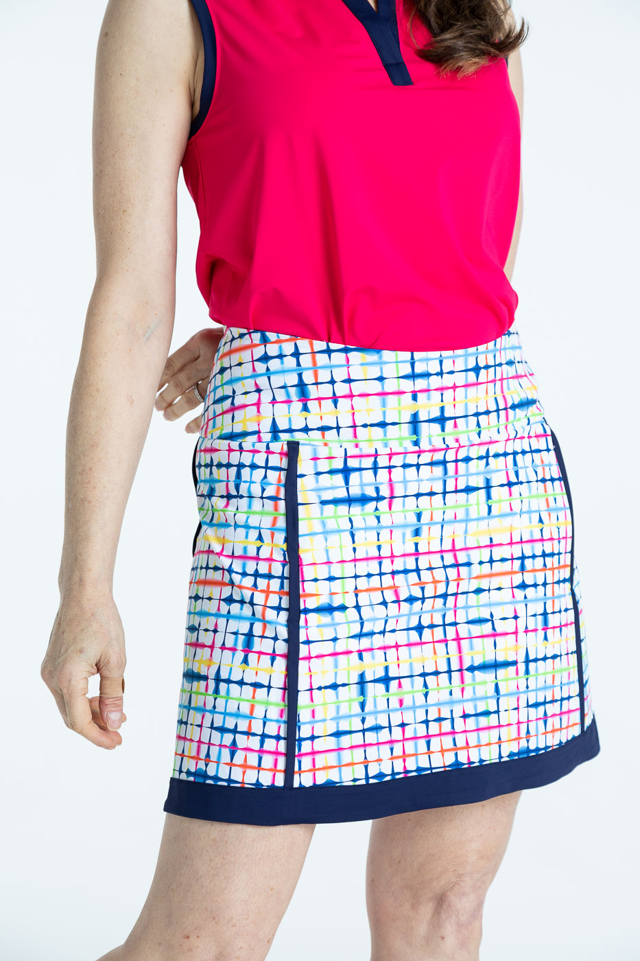 Back view of woman wearing a blurred lines Fresh and Flirty golf skort with a raspberry red Free and Easy sleeveless golf shirt