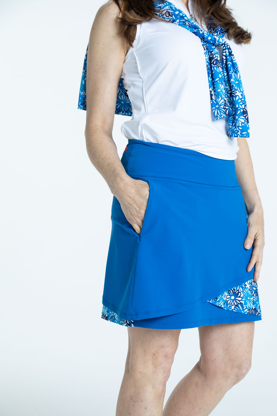 Side view of woman wearing a blueberry blue Wrap it Up golf skort and a white/white Keep it Covered sleeveless golf top