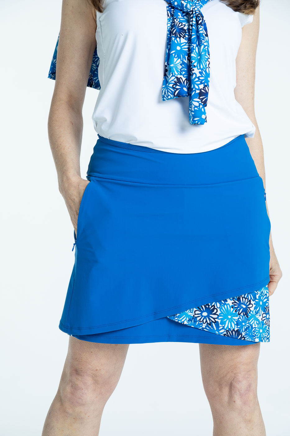 Closer front view of woman wearing a blueberry blue Wrap it Up golf skort and a white/white Keep it Covered sleeveless golf top
