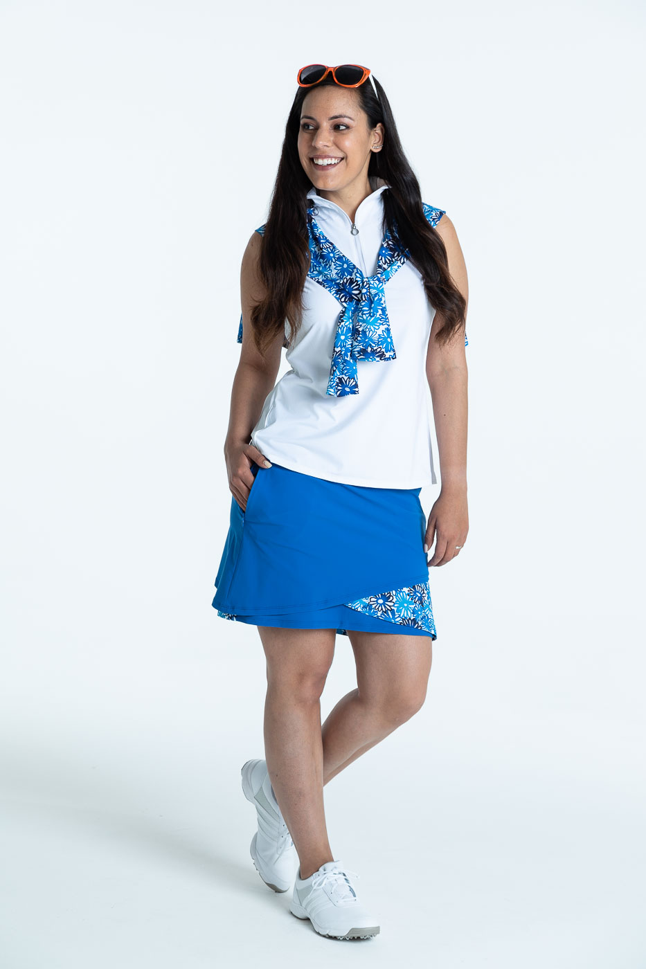 Smiling woman wearing a blueberry blue Wrap it Up golf skort and a white/white Keep it Covered sleeveless golf top