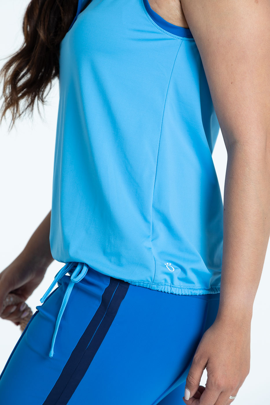 Side view of blueberry blue Tailored Track golf pants with a cornflower blue Free and Easy sleeveless golf top