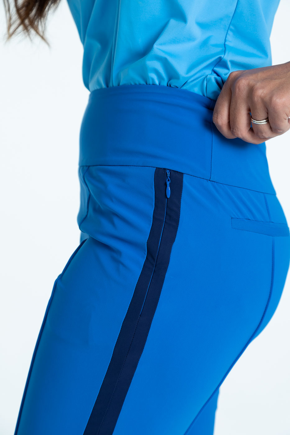 Closer side view of blueberry blue Tailored Track golf pants with a cornflower blue Free and Easy sleeveless golf top
