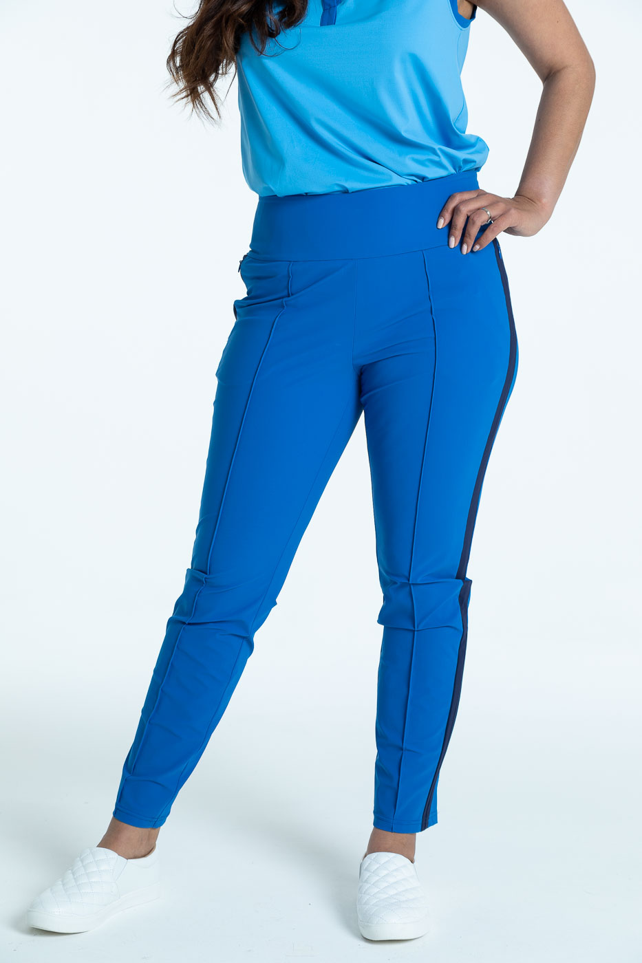 Woman golfer in  blueberry blue Tailored Track golf pants with a cornflower blue Free and Easy sleeveless golf top
