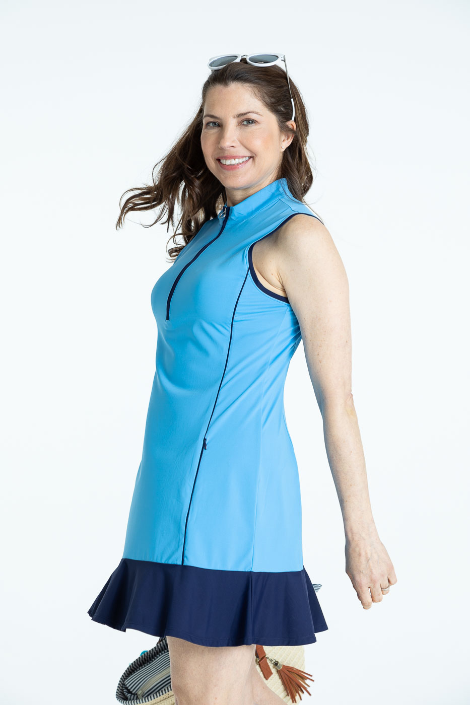 Side view of woman golfer in a cornflower blue Fit and Flare sleeveless golf dress