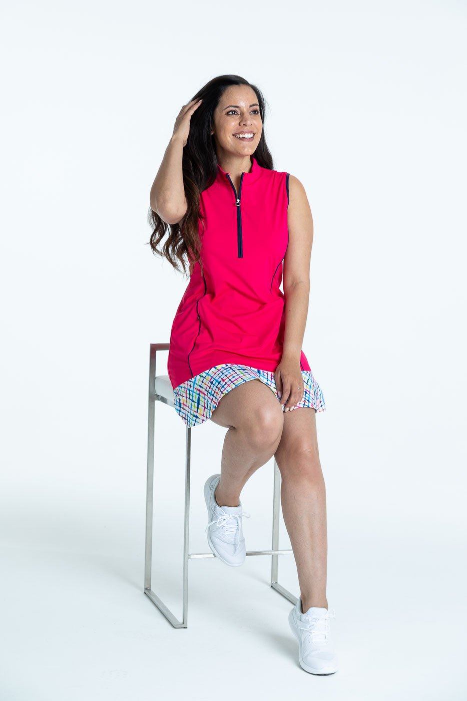 Smiling woman in a raspberry red Fit and Flare sleeveless golf dress