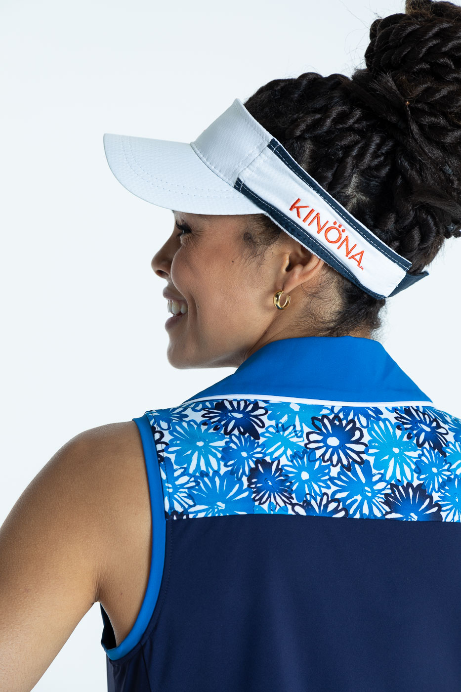 Close-up back view of the top of the navy blue Chip Shot sleeveless golf dress and a white No Hat Hair Visor