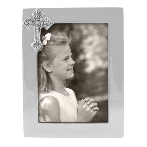 Cross 5 x 7 Frame  This Cross Frame makes an outstanding christening or First Communion gift. Commemorate a religious milestone in this handcrafted frame with delicate cross accent. Recycled Sandcast Aluminum DETAILS & PRODUCT CARE  Dimensions: 8.75in L x 6.75in W Product Care: Our fine metal is handcrafted from 100% recycled aluminum. All items are food-safe and will not tarnish. Handwash in warm water with mild soap and towel dry immediately. Do not place in dishwasher or microwave. Avoid extended contact with water, salty or acidic foods; coat lightly with vegetable oil or spray to easily avoid staining. Warm to 350 degerees for hot foods. Freeze or chill for summer entertaining. Cutting directly on the metal surface will scratch the finish. Occasional use of non-abrasive metal polish will revive luster.