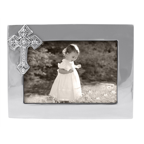 Cross 4 x 6 Frame  Cross Frame is an excellent christening or first communion gift. Commemorate a religious milestone in this handcrafted frame with delicate cross accent. Recycled Sandcast Aluminum DETAILS & PRODUCT CARE  Dimensions: 7.5in L x 5.5in W Product Care: Our fine metal is handcrafted from 100% recycled aluminum. All items are food-safe and will not tarnish. Handwash in warm water with mild soap and towel dry immediately. Do not place in dishwasher or microwave. Avoid extended contact with water, salty or acidic foods; coat lightly with vegetable oil or spray to easily avoid staining. Warm to 350 degerees for hot foods. Freeze or chill for summer entertaining. Cutting directly on the metal surface will scratch the finish. Occasional use of non-abrasive metal polish will revive luster.