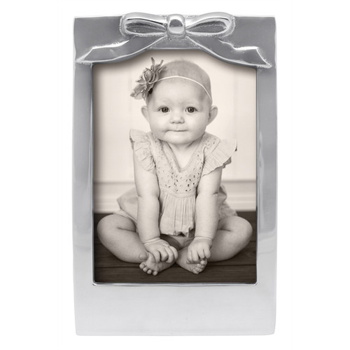 Bow 5 x 7 Frame  An adorable, sculpted Bow adorns this handcrafted and 100% recycled 5x7 Frame. Display an equally adorable picture of your child or grandchild. Engraveable. Recycled Sandcast Aluminum DETAILS & PRODUCT CARE  Dimensions: 5.6in L x 8.9in W Product Care: Our fine metal is handcrafted from 100% recycled aluminum. All items are food-safe and will not tarnish. Handwash in warm water with mild soap and towel dry immediately. Do not place in dishwasher or microwave. Avoid extended contact with water, salty or acidic foods; coat lightly with vegetable oil or spray to easily avoid staining. Warm to 350 degerees for hot foods. Freeze or chill for summer entertaining. Cutting directly on the metal surface will scratch the finish. Occasional use of non-abrasive metal polish will revive luster.