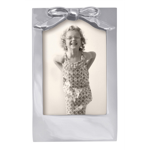 Bow 4 x 6 Frame  An adorable, sculpted Bow adorns this handcrafted and 100% recycled 4x6 Frame. Display an equally adorable picture of your child or grandchild. Engraveable. Recycled Sandcast Aluminum DETAILS & PRODUCT CARE  Dimensions: 4.65in L x 1in W x 7.48in H Product Care: Our fine metal is handcrafted from 100% recycled aluminum. All items are food-safe and will not tarnish. Handwash in warm water with mild soap and towel dry immediately. Do not place in dishwasher or microwave. Avoid extended contact with water, salty or acidic foods; coat lightly with vegetable oil or spray to easily avoid staining. Warm to 350 degerees for hot foods. Freeze or chill for summer entertaining. Cutting directly on the metal surface will scratch the finish. Occasional use of non-abrasive metal polish will revive luster.
