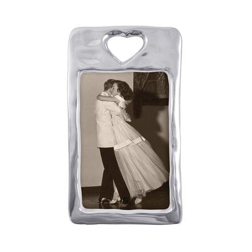 Open Heart 4 x 6 Frame  Softly textured 4 x 6 vertical frame features an open heart cut-out at the top. Display a special moment with a loved one in this delicately organic photo frame. Recycled Sandcast Aluminum DETAILS & PRODUCT CARE  Dimensions: 8in L x 4.75in W Product Care: Our fine metal is handcrafted from 100% recycled aluminum. All items are food-safe and will not tarnish. Handwash in warm water with mild soap and towel dry immediately. Do not place in dishwasher or microwave. Avoid extended contact with water, salty or acidic foods; coat lightly with vegetable oil or spray to easily avoid staining. Warm to 350 degerees for hot foods. Freeze or chill for summer entertaining. Cutting directly on the metal surface will scratch the finish. Occasional use of non-abrasive metal polish will revive luster.
