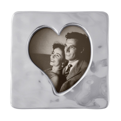 Small Square Open Heart Frame  A small, softly textured frame allows a photo of you and a loved one to peak out through the heart opening. Part of the First Comes Loves collection which celebrates the eternal reign of romance. Recycled Sandcast Aluminum DETAILS & PRODUCT CARE  Dimensions: 4.5in L x 4.5in H Product Care: Our fine metal is handcrafted from 100% recycled aluminum. All items are food-safe and will not tarnish. Handwash in warm water with mild soap and towel dry immediately. Do not place in dishwasher or microwave. Avoid extended contact with water, salty or acidic foods; coat lightly with vegetable oil or spray to easily avoid staining. Warm to 350 degerees for hot foods. Freeze or chill for summer entertaining. Cutting directly on the metal surface will scratch the finish. Occasional use of non-abrasive metal polish will revive luster. Photo Opening Size: 4 x 6