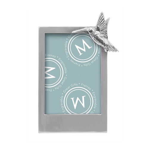 Adorned with a delightful hummingbird, the Hummingbird 5x7 Frame is the ideal gift for nature lovers. Personalize with a name, date, or favorite saying. Handcrafted from 100% recycled aluminum. Recycled Sandcast Aluminum DETAILS & PRODUCT CARE Item Code: 2468 Dimensions: 6.73in L x 1in W x 10.04in H Product Care: Our fine metal is handcrafted from 100% recycled aluminum. All items are food-safe and will not tarnish. Handwash in warm water with mild soap and towel dry immediately. Do not place in dishwasher or microwave. Avoid extended contact with water, salty or acidic foods; coat lightly with vegetable oil or spray to easily avoid staining. Warm to 350 degerees for hot foods. Freeze or chill for summer entertaining. Cutting directly on the metal surface will scratch the finish. Occasional use of non-abrasive metal polish will revive luster.