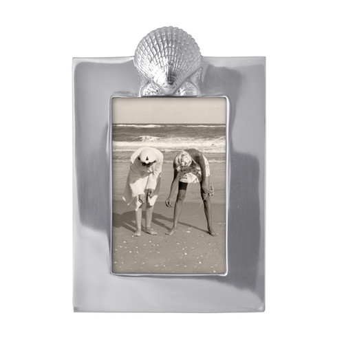 Preserve memories of sun and sand in our Scallop Frame. Part of our Seaside collection, this frame fits a 4 x 6 photo. Recycled Sandcast Aluminum DETAILS & PRODUCT CARE Item Code: 2166 Dimensions: 9in L x 6in H Product Care: Our fine metal is handcrafted from 100% recycled aluminum. All items are food-safe and will not tarnish. Handwash in warm water with mild soap and towel dry immediately. Do not place in dishwasher or microwave. Avoid extended contact with water, salty or acidic foods; coat lightly with vegetable oil or spray to easily avoid staining. Warm to 350 degerees for hot foods. Freeze or chill for summer entertaining. Cutting directly on the metal surface will scratch the finish. Occasional use of non-abrasive metal polish will revive luster. Photo Opening Size: 4 x 6