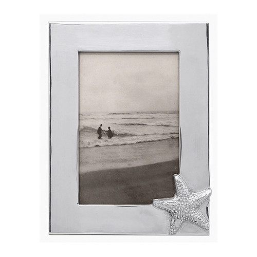 Preserve memories of sun and sand in our Starfish Frame. Part of our Seaside collection, this frame fits a 4 x 6 photo. Recycled Sandcast Aluminum DETAILS & PRODUCT CARE Item Code: 1213 Dimensions: 8in L x 6in H Product Care: Our fine metal is handcrafted from 100% recycled aluminum. All items are food-safe and will not tarnish. Handwash in warm water with mild soap and towel dry immediately. Do not place in dishwasher or microwave. Avoid extended contact with water, salty or acidic foods; coat lightly with vegetable oil or spray to easily avoid staining. Warm to 350 degerees for hot foods. Freeze or chill for summer entertaining. Cutting directly on the metal surface will scratch the finish. Occasional use of non-abrasive metal polish will revive luster. Photo Opening Size: 4 x 6