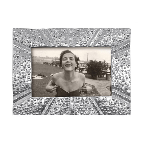 Bring undersea treasures to your home with our highly decorative Sea Urchin Textured 4x6 Frame. Beautifully handcrafted from 100% recycled aluminum with subtle textures translated from the surface of the sea urchin. Recycled Sandcast Aluminum DETAILS & PRODUCT CARE Item Code: 3446 Dimensions: 9.5in L x 1in W x 7.75in H Product Care: Our fine metal is handcrafted from 100% recycled aluminum. All items are food-safe and will not tarnish. Handwash in warm water with mild soap and towel dry immediately. Do not place in dishwasher or microwave. Avoid extended contact with water, salty or acidic foods; coat lightly with vegetable oil or spray to easily avoid staining. Warm to 350 degerees for hot foods. Freeze or chill for summer entertaining. Cutting directly on the metal surface will scratch the finish. Occasional use of non-abrasive metal polish will revive luster.