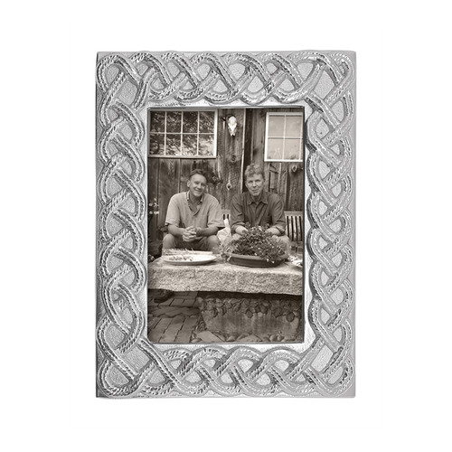 Intertwining sailing rope forms an open braid and creates a handsome border to frame your 4x6 photo. This intricate design is perfect for him or her, especially those with an affinity for the high seas. Handcrafted from 100% recycled aluminum. Recycled Sandcast Aluminum DETAILS & PRODUCT CARE Item Code: 2266 Dimensions: 8.31in L x 1in W x 6.34in H Product Care: Our fine metal is handcrafted from 100% recycled aluminum. All items are food-safe and will not tarnish. Handwash in warm water with mild soap and towel dry immediately. Do not place in dishwasher or microwave. Avoid extended contact with water, salty or acidic foods; coat lightly with vegetable oil or spray to easily avoid staining. Warm to 350 degerees for hot foods. Freeze or chill for summer entertaining. Cutting directly on the metal surface will scratch the finish. Occasional use of non-abrasive metal polish will revive luster.