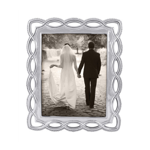 Delicate, openwork dances around the borders of textured serving pieces and gifts in our Filigree collection. Display a photo of your big day, or any truly special moment, in our elegant 8 x 10 inch Filigree Frame. Recycled Sandcast Aluminum DETAILS & PRODUCT CARE Item Code: 3678 Dimensions: 12.75in L x 10.75in W Product Care: Our fine metal is handcrafted from 100% recycled aluminum. All items are food-safe and will not tarnish. Handwash in warm water with mild soap and towel dry immediately. Do not place in dishwasher or microwave. Avoid extended contact with water, salty or acidic foods; coat lightly with vegetable oil or spray to easily avoid staining. Warm to 350 degerees for hot foods. Freeze or chill for summer entertaining. Cutting directly on the metal surface will scratch the finish. Occasional use of non-abrasive metal polish will revive luster.