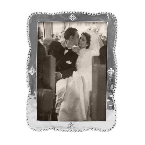 """Our Sueño collection is a romantic reverie in softly textured, beaded (and recycled!) aluminum. Display a photo of your favorite romantic moment in elegant style. 5 x 7"""" is the largest size available in the Sueño frame series. Recycled Sandcast Aluminum DETAILS & PRODUCT CARE Item Code: 3655 Dimensions: 8.25in L x 6.25in W Product Care: Our fine metal is handcrafted from 100% recycled aluminum. All items are food-safe and will not tarnish. Handwash in warm water with mild soap and towel dry immediately. Do not place in dishwasher or microwave. Avoid extended contact with water, salty or acidic foods; coat lightly with vegetable oil or spray to easily avoid staining. Warm to 350 degerees for hot foods. Freeze or chill for summer entertaining. Cutting directly on the metal surface will scratch the finish. Occasional use of non-abrasive metal polish will revive luster. Photo Opening Size: 5 x 7"""