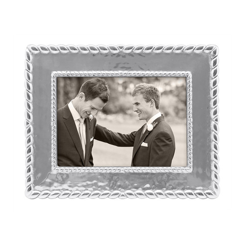 Our luxe Meridian 5 x 7 Frame evokes style and gives a fresh, sophisticated look to a cherished photograph. Recycled Sandcast Aluminum DETAILS & PRODUCT CARE  Dimensions: 10.75in L x 8.75in W Product Care: Our fine metal is handcrafted from 100% recycled aluminum. All items are food-safe and will not tarnish. Handwash in warm water with mild soap and towel dry immediately. Do not place in dishwasher or microwave. Avoid extended contact with water, salty or acidic foods; coat lightly with vegetable oil or spray to easily avoid staining. Warm to 350 degerees for hot foods. Freeze or chill for summer entertaining. Cutting directly on the metal surface will scratch the finish. Occasional use of non-abrasive metal polish will revive luster.