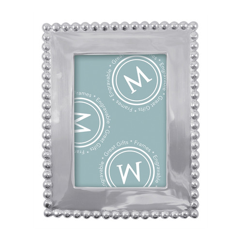 A classic frame with a solid border, edged with beaded trim. Part of our signature String of Pearls collection, this frame fits a 5 x 7 inch photo. Recycled Sandcast Aluminum DETAILS & PRODUCT CARE Dimensions: 10in L x 8in W Product Care: Our fine metal is handcrafted from 100% recycled aluminum. All items are food-safe and will not tarnish. Handwash in warm water with mild soap and towel dry immediately. Do not place in dishwasher or microwave. Avoid extended contact with water, salty or acidic foods; coat lightly with vegetable oil or spray to easily avoid staining. Warm to 350 degerees for hot foods. Freeze or chill for summer entertaining. Cutting directly on the metal surface will scratch the finish. Occasional use of non-abrasive metal polish will revive luster. Photo Opening Size: 5 x 7