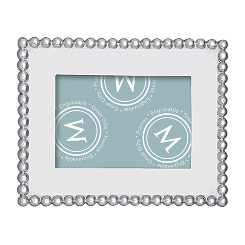 A classic frame with a solid border, edged with beaded trim. Part of our signature String of Pearls collection, this frame fits a 4 x 6 inch photo. Recycled Sandcast Aluminum DETAILS & PRODUCT CARE Dimensions: 9in L x 7in W Product Care: Our fine metal is handcrafted from 100% recycled aluminum. All items are food-safe and will not tarnish. Handwash in warm water with mild soap and towel dry immediately. Do not place in dishwasher or microwave. Avoid extended contact with water, salty or acidic foods; coat lightly with vegetable oil or spray to easily avoid staining. Warm to 350 degerees for hot foods. Freeze or chill for summer entertaining. Cutting directly on the metal surface will scratch the finish. Occasional use of non-abrasive metal polish will revive luster. Photo Opening Size: 4 x 6