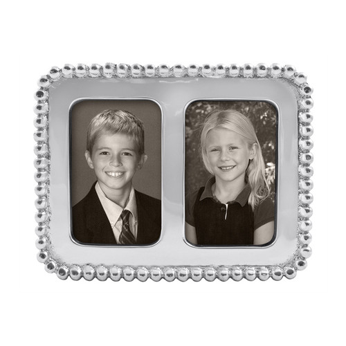 "Gleaming Beaded Double 2 x 3"" Frame, part of our signature String of Pearls collection. Add two school photos or another favorite set of wallet-size snapshots. Recycled Sandcast Aluminum DETAILS & PRODUCT CARE Dimensions: 5.25in L x 4in W Product Care: Our fine metal is handcrafted from 100% recycled aluminum. All items are food-safe and will not tarnish. Handwash in warm water with mild soap and towel dry immediately. Do not place in dishwasher or microwave. Avoid extended contact with water, salty or acidic foods; coat lightly with vegetable oil or spray to easily avoid staining. Warm to 350 degerees for hot foods. Freeze or chill for summer entertaining. Cutting directly on the metal surface will scratch the finish. Occasional use of non-abrasive metal polish will revive luster."