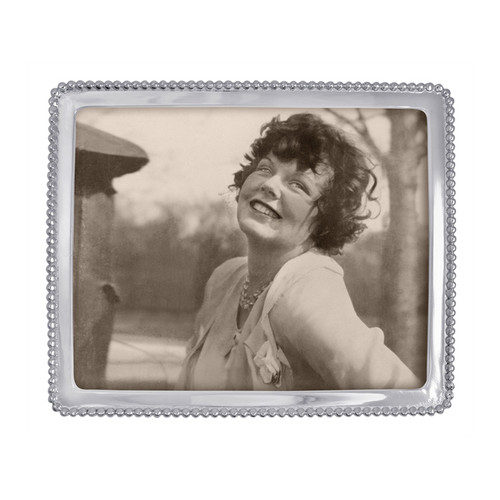 Display cherished moments with style and timeless appeal in our Large Beaded Edge Frame. Part of our signature String of Pearls collection. Recycled Sandcast Aluminum DETAILS & PRODUCT CARE Dimensions: 11in L x 9in W Product Care: Our fine metal is handcrafted from 100% recycled aluminum. All items are food-safe and will not tarnish. Handwash in warm water with mild soap and towel dry immediately. Do not place in dishwasher or microwave. Avoid extended contact with water, salty or acidic foods; coat lightly with vegetable oil or spray to easily avoid staining. Warm to 350 degerees for hot foods. Freeze or chill for summer entertaining. Cutting directly on the metal surface will scratch the finish. Occasional use of non-abrasive metal polish will revive luster. Photo Opening Size: 8 x 10