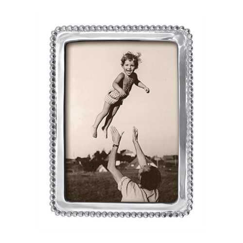 A classic frame with beaded trim, perfect for your favorite snapshot. Part of the classic String of Pearls collection. Recycled Sandcast Aluminum DETAILS & PRODUCT CARE Dimensions: 8in L x 6in W Product Care: Our fine metal is handcrafted from 100% recycled aluminum. All items are food-safe and will not tarnish. Handwash in warm water with mild soap and towel dry immediately. Do not place in dishwasher or microwave. Avoid extended contact with water, salty or acidic foods; coat lightly with vegetable oil or spray to easily avoid staining. Warm to 350 degerees for hot foods. Freeze or chill for summer entertaining. Cutting directly on the metal surface will scratch the finish. Occasional use of non-abrasive metal polish will revive luster. Photo Opening Size: 5 x 7