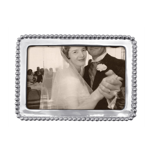 A classic frame with beaded trim, perfect for your favorite snapshot. Part of the classic String of Pearls collection. Recycled Sandcast Aluminum DETAILS & PRODUCT CARE Dimensions: 7in L x 5in W Product Care: Our fine metal is handcrafted from 100% recycled aluminum. All items are food-safe and will not tarnish. Handwash in warm water with mild soap and towel dry immediately. Do not place in dishwasher or microwave. Avoid extended contact with water, salty or acidic foods; coat lightly with vegetable oil or spray to easily avoid staining. Warm to 350 degerees for hot foods. Freeze or chill for summer entertaining. Cutting directly on the metal surface will scratch the finish. Occasional use of non-abrasive metal polish will revive luster. Photo Opening Size: 4 x 6
