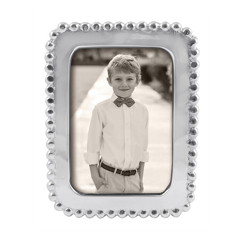 Display school pictures or other wallet-size snapshots in the Beaded 2 x 3 Frame. Handcrafted from sparkling, 100% recycled aluminum. Recycled Sandcast Aluminum DETAILS & PRODUCT CARE Dimensions: 4.5in L x 3.5in W Product Care: Our fine metal is handcrafted from 100% recycled aluminum. All items are food-safe and will not tarnish. Handwash in warm water with mild soap and towel dry immediately. Do not place in dishwasher or microwave. Avoid extended contact with water, salty or acidic foods; coat lightly with vegetable oil or spray to easily avoid staining. Warm to 350 degerees for hot foods. Freeze or chill for summer entertaining. Cutting directly on the metal surface will scratch the finish. Occasional use of non-abrasive metal polish will revive luster. Photo Opening Size: 2 x 3