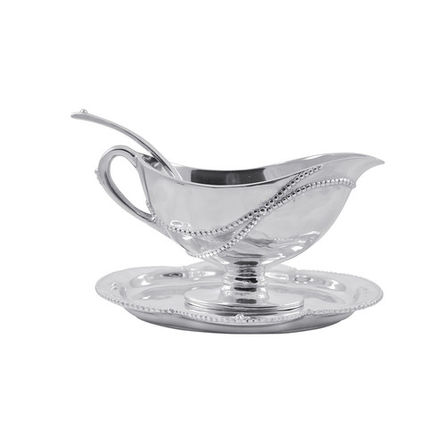 Our Sueño collection is a romantic reverie in softly textured, beaded (and recycled!) aluminum. Complete with matching tray and spoon, the Sueño Gravy Boat Set elegantly emphasizes organic textures and flowing contours. Set makes a lovely wedding gift! Recycled Sandcast Aluminum DETAILS & PRODUCT CARE Dimensions: 7in L x 5.5in W x 4in H Product Care: Our fine metal is handcrafted from 100% recycled aluminum. All items are food-safe and will not tarnish. Handwash in warm water with mild soap and towel dry immediately. Do not place in dishwasher or microwave. Avoid extended contact with water, salty or acidic foods; coat lightly with vegetable oil or spray to easily avoid staining. Warm to 350 degerees for hot foods. Freeze or chill for summer entertaining. Cutting directly on the metal surface will scratch the finish. Occasional use of non-abrasive metal polish will revive luster.