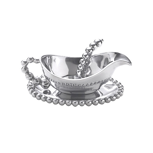 We have a gift for tradition, reimagined, in our String of Pearls collection. A wealth of luxurious pearls and elegant contours form the gravy boat, small plate and spoon in this brilliant serveware set. Recycled Sandcast Aluminum DETAILS & PRODUCT CARE Dimensions: 7in L x 5in W Product Care: Our fine metal is handcrafted from 100% recycled aluminum. All items are food-safe and will not tarnish. Handwash in warm water with mild soap and towel dry immediately. Do not place in dishwasher or microwave. Avoid extended contact with water, salty or acidic foods; coat lightly with vegetable oil or spray to easily avoid staining. Warm to 350 degerees for hot foods. Freeze or chill for summer entertaining. Cutting directly on the metal surface will scratch the finish. Occasional use of non-abrasive metal polish will revive luster.
