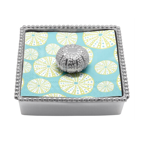 Mariposa Sea Urchin Napkin Box  4028-C  5.75in L x 5.75in W x 1.5in H  Our Sea Urchin Beaded Napkin Box is the perfect compliment to your nautical or beach table. Includes a stack of intricately patterned, blue and white sea urchin cocktail napkins. Handcrafted from 100% recycled aluminum. Recycled Sandcast Aluminum