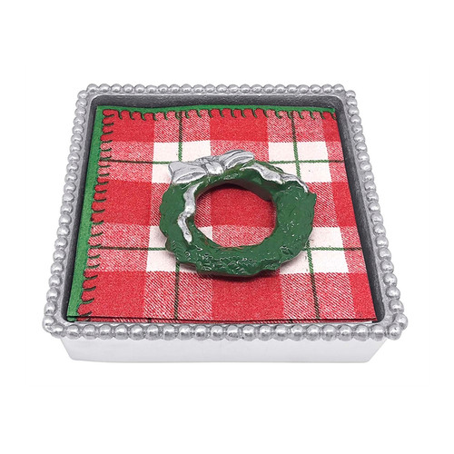 Mariposa Green Wreath Napkin Box   1589C 5.75in L x 5.75in W x 1.5in H  Bring holiday cheer to your next gathering with our Green Wreath Beaded Napkin Box. This set includes a napkin box, stack of festive cocktail napkins and a decorative Green Wreath Napkin Weight. Handcrafted from 100% recycled aluminum Recycled Sandcast Aluminum
