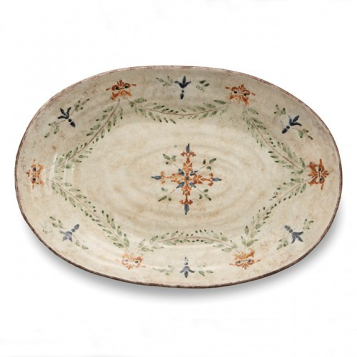 "The gentle cream color of this platter is accented with a beautiful, hand-painted giglio (fleur-de-lis) and vine motif in rich hues of green, blue and orange. The uneven edges and subtle colors add to the old world look. Italian ceramic, Hand made in Italy.  Microwaveable (may get hot) and dishwasher safe on the low heat, air-dry setting.  Dimensions: 20"" L x 14"" W SKU: MED2450"