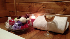 A glass of white wine, bath bombs in a bowl back-lit by a candle, on a wood bathtub ledge with a white towel.