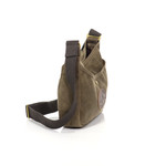 The Large Crescent Lake Shoulder Bag has a front slip pocket that is able to be sealed with a snap.