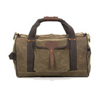 Explorer Duffel by Frost River is made from 'field tan' colored waxed canvas. It comes with a shoulder strap and wide green cotton webbing.