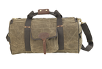 The medium Explorer Duffel by Frost River is made from 'field tan' colored waxed canvas. It comes with a shoulder strap and wide green cotton webbing.