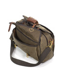 The large pockets of the front and back are made of waxed canvas and secured shut with leather straps and solid brass hardware.