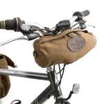 The Sawbill Trail Handlebar Bag attaches to the bike on the handlebars with two leather straps. This product is made in America by Frost River.