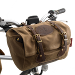 The Caribou Bike Bag is versatile and can be worn on the handle bars or on the back of the seat. Its high quality materials include leather, solid brass hardware, and waxed canvas.