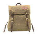 The book pack has a gusset and is made from waxed canvas, leather, and solid brass hardware.