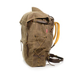 This pack is crafted from the best materials including leather, padded buckskin shoulder straps, waxed canvas, and solid brass hardware. A side profile shows laced cord which is a versatile feature that can hold extra gear or sinch in the side of the bag.