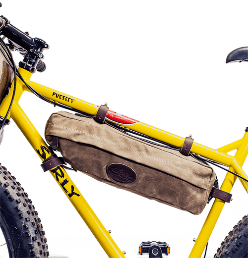 The Trezona Trail Top Tube Bag attaches to the frame of the bike with leather straps and solid brass hardware. This product is made in the USA at Frost River from waxed canvas.