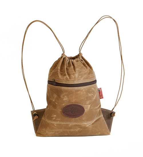 Ima Lake Cinch Bag in Field Tan is made of waxed canvas that is water resistant. The zipper on the front is durable and will last a lifetime.