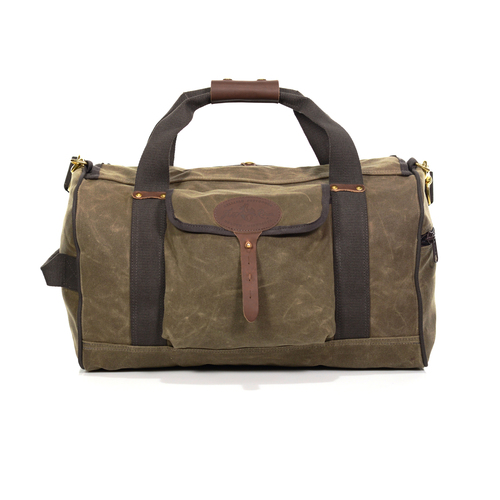 The carry-on Explorer Duffel by Frost River is made from 'field tan' colored waxed canvas. It comes with a shoulder strap and wide green cotton webbing.