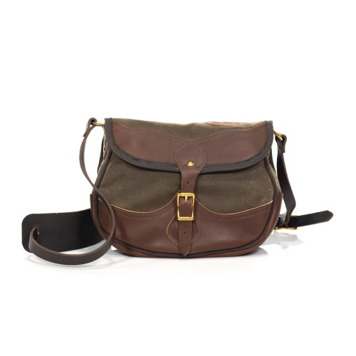"""The premium shell bag is a """"luxury"""" version of the shell bag. It has a leather bottom, leather flap, and a leather strap."""
