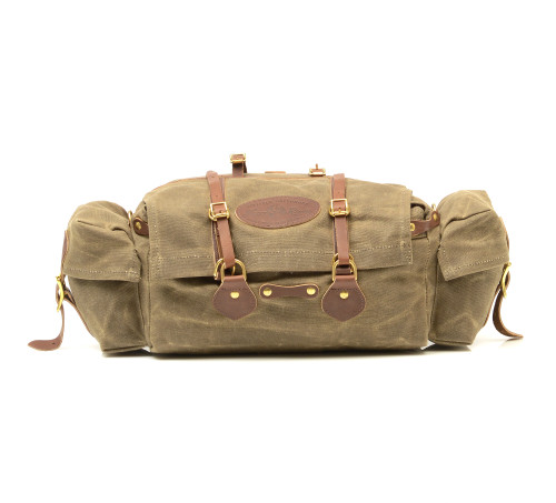 This versatile pack is made of waxed canvas, premium leather, and solid brass hardware. The Gunflint Trail Seat Bag can be attached to your seat or have a strap fastened by the D-rings when not peddling.